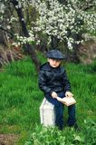 Portrait of a boy with a book in the spring blooming garden royalty free stock photography
