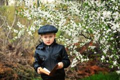 Portrait of a boy with a book in the spring blooming garden royalty free stock images