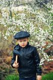 Portrait of a boy with a book in the spring blooming garden royalty free stock photos