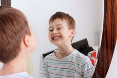 Portrait of a boy. boy shows tongue. Portrait of a boy. He stands in front of the mirror and is done. The boy trains articulation. Speech training stock image