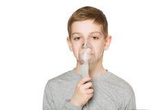 Portrait of a boy breathing through inhalator mask isolated on w Stock Image