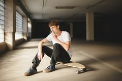 Boy with brown hair sitting on skateboard and thoughtfully looking down while smoking. Photo of young man in white t. Portrait of boy with brown hair sitting on Royalty Free Stock Photo