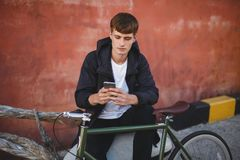 Boy with brown hair sitting and using his cellphone. Young thoughtful man in down jacket and white t-shirt sitting with. Portrait of boy with brown hair sitting Stock Images