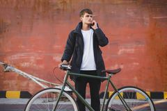 Boy with brown hair standing with classic bicycle and thoughtfully looking aside while talking on his cellphone. Young. Portrait of boy with brown hair standing Royalty Free Stock Photo