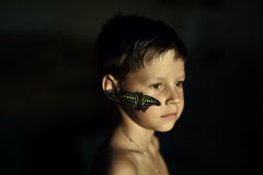 Portrait of a boy with a butterfly. On a black background portrait of a boy with a big and beautiful butterfly on her face Stock Image