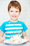 Portrait of a boy with a cake and candles. Stock Photography