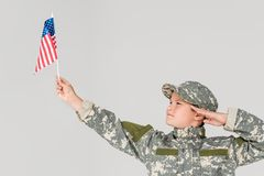 Portrait of boy in camouflage clothing saluting and looking at american flagpole in hand. Isolated on grey royalty free stock photo