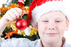 Portrait of a boy in a cap of Santa Claus. Portrait of a boy on the background of the Christmas tree Stock Photography