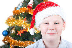Portrait of a boy in a cap of Santa Claus. Portrait of a boy on the background of the Christmas tree Stock Photo