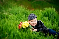 Portrait of a boy , a child holding a bouquet of flowers. Lying on grass Stock Image