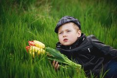 Portrait of a boy , a child holding a bouquet of flowers. Lying on grass Royalty Free Stock Images
