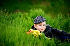 Portrait of a boy , a child holding a bouquet of flowers. Lying on grass Royalty Free Stock Photos