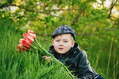 Portrait of a boy , a child holding a bouquet of flowers. Sitting on the grass Royalty Free Stock Photo