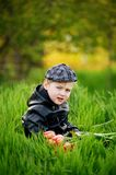 Portrait of a boy , a child holding a bouquet of flowers. Sitting on the grass Stock Photo