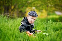 Portrait of a boy , a child holding a bouquet of flowers. Sitting on the grass Royalty Free Stock Image