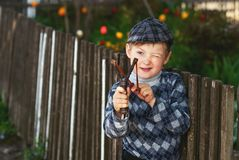 Portrait of a boy , a child holding a slingshot. Little hooligan Royalty Free Stock Photos