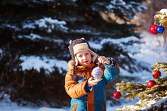 Portrait of a boy with christmas ball walking in the winter nature. Playing with snow. Concept happy childhood Stock Photo