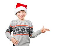 Portrait of a boy in christmas hat pointing at Stock Photos