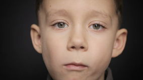 Portrait of a boy close-up on a black background stock footage