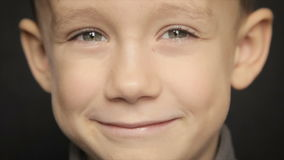 Portrait of a boy close-up on a black background. Full hd video. Portrait of a boy close-up on a black background. Slow motion stock video