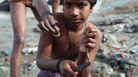 Portrait of boy at dirty shore of Ganges river, with other standing behind him. stock video