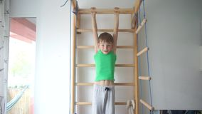 Portrait of a boy doing exercise on abdominal muscles on the horizontal bar. Portrait of a boy doing an exercise on abdominal muscles on a horizontal bar in a stock footage