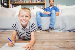 Portrait of boy drawing in book while father sitting on sofa Royalty Free Stock Photography