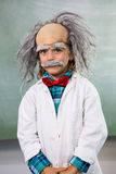 Portrait of boy dressed as scientist standing against board. In classroom Stock Image