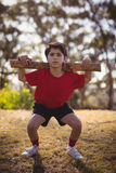 Portrait boy exercising with log during obstacle course royalty free stock image