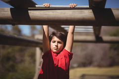 Portrait of boy exercising on monkey bar during obstacle course. In boot camp Royalty Free Stock Photography