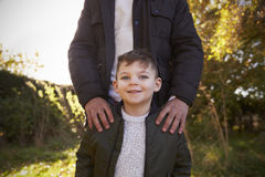 Portrait Of Boy With Father Standing In Autumn Garden Stock Photo