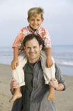 Portrait of boy on fathers shoulders at beach royalty free stock image