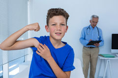 Portrait of boy flexing his biceps in the clinic Stock Images