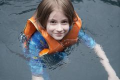 Portrait of a boy floating in a lifejacket. In the pool Stock Photo
