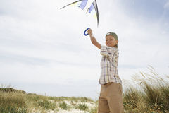 Portrait Of Boy Flying Kite On A Windy Beach Stock Photography