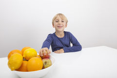 Portrait of boy with fruit bowl at table Royalty Free Stock Photography
