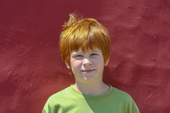 Portrait of Boy with ginger hair in front of a red wall Royalty Free Stock Photography