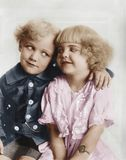 Portrait of a boy and girl with arm around her stock photo