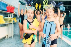 Portrait of boy and girl with colorful flippers. In hands near swimming pool. Sportive healthy children after swimming exercises. Happy kids in modern sport Stock Photography