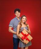 Portrait of a boy and a girl with a gift in a pin up style, isol. Portrait of a boy and a girl with a gift in a pin up style,  on a red background Stock Photos
