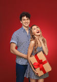 Portrait of a boy and a girl with a gift in a pin up style, isol. Portrait of a boy and a girl with a gift in a pin up style,  on a red background Royalty Free Stock Image