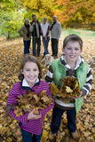 Portrait of boy and girl holding autumn leaves with family in background Stock Image