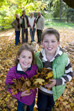 Portrait of boy and girl holding autumn leaves with family in background Royalty Free Stock Photos