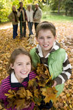 Portrait of boy and girl holding autumn leaves with family in background Royalty Free Stock Photo