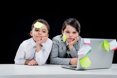 Portrait of boy and girl with notes on faces sitting at workplace Stock Images