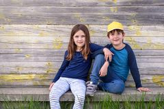 Portrait of boy and girl sitting in the street of suburb. Friendship Royalty Free Stock Image