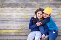 Portrait of boy and girl sitting in the street of suburb. Friendship Royalty Free Stock Photo