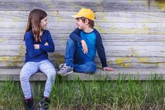 Portrait of boy and girl sitting in the street of suburb. Friendship Royalty Free Stock Photos