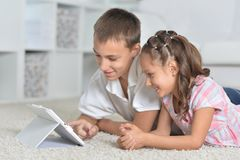 Portrait of boy and girl with tablet pc stock photography