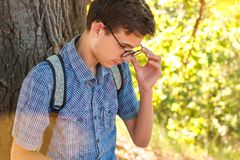 Portrait of a boy in glasses nerd on a tree background royalty free stock images